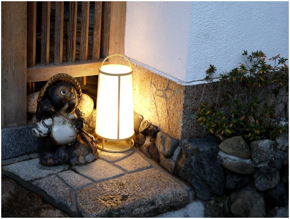 Pottery tanuki beside lamp on doorstep