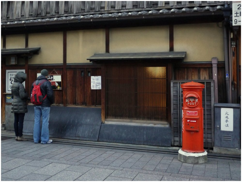 Postbox outside traditional Japanese building