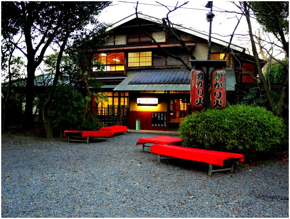 Red benches outside Japanese restaurant in evening
