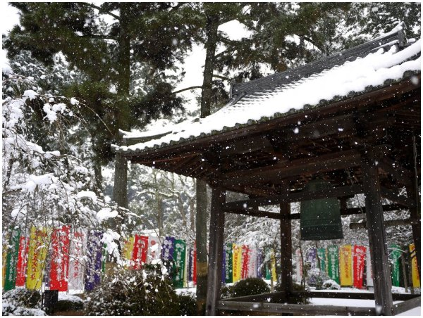 Bell tower & banners in snow at Japanese temple