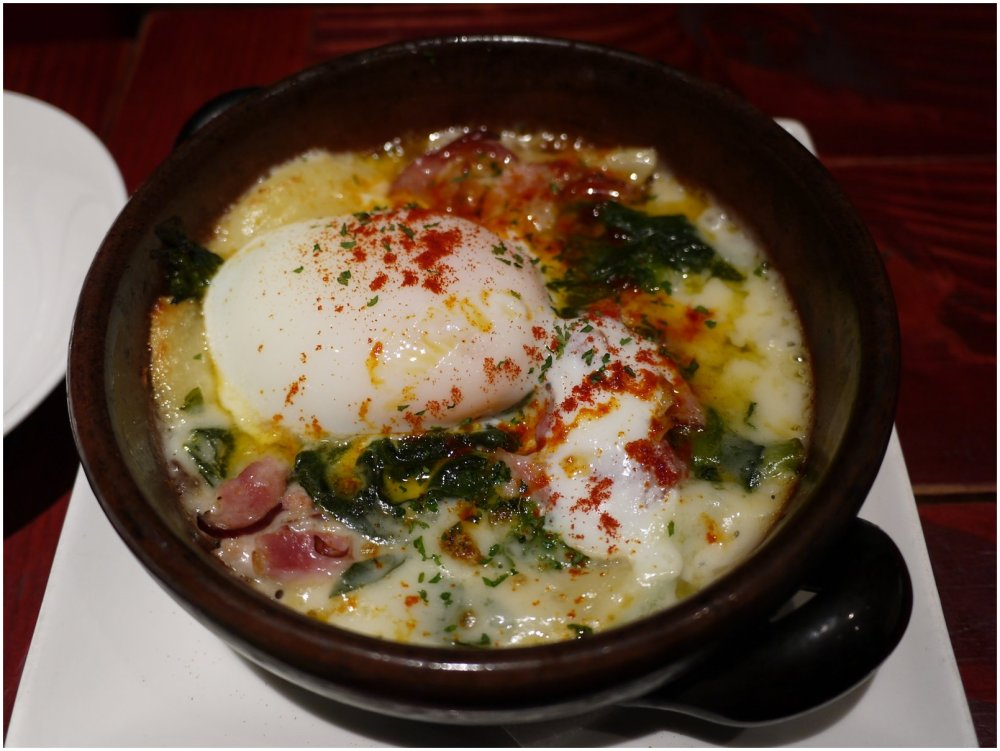 Cast iron dish of doria, topped with egg