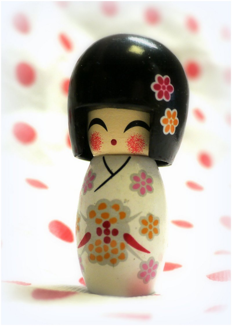 Japanese kokeshi doll on a polkadot background