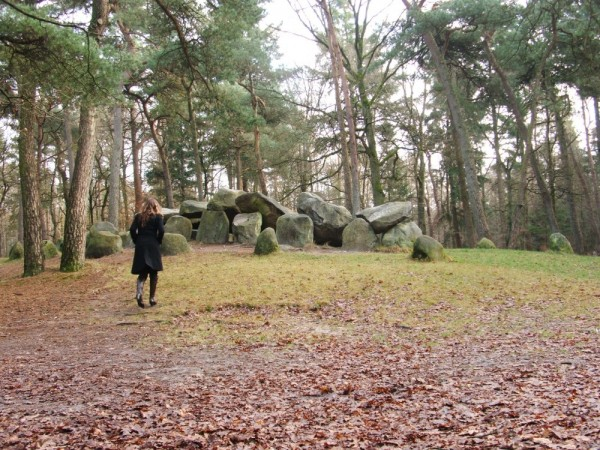 Lonely woman walking in forest nearby a dolmen.