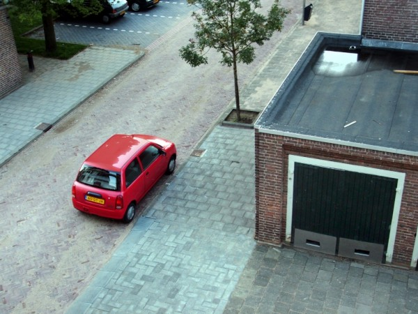 A small, parked, red, car.