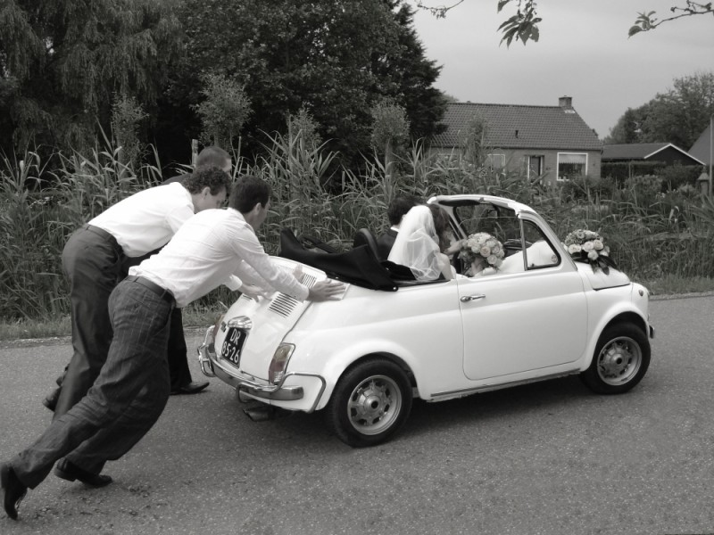 Men pushing wedding car