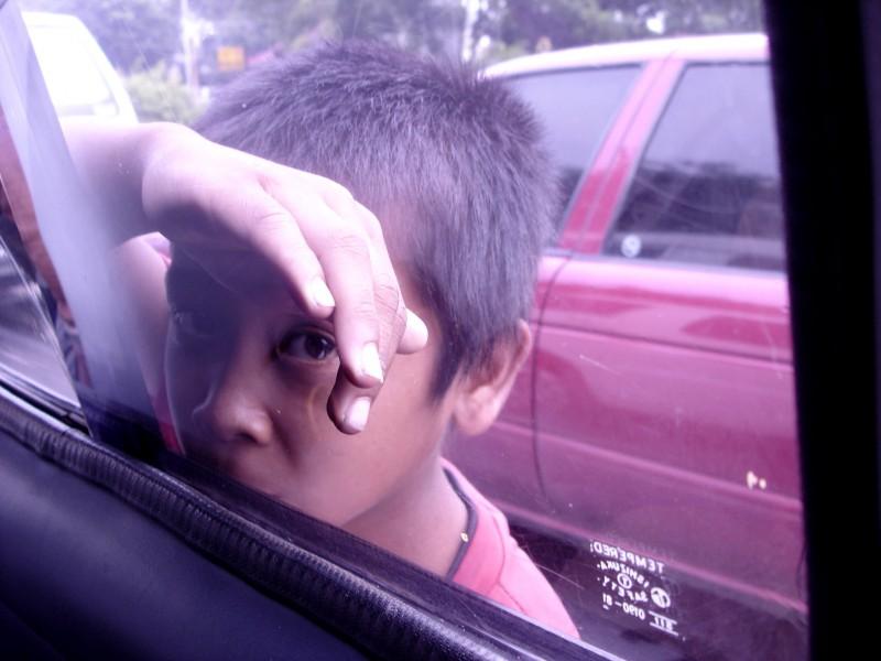 poor kid looking through car window