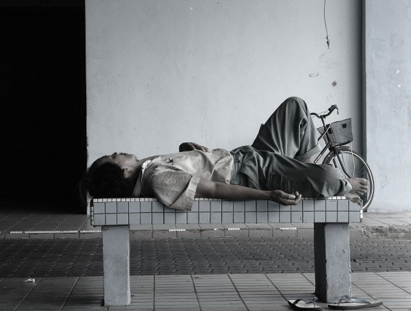 a homeless guy sleeping on a bus stop bench