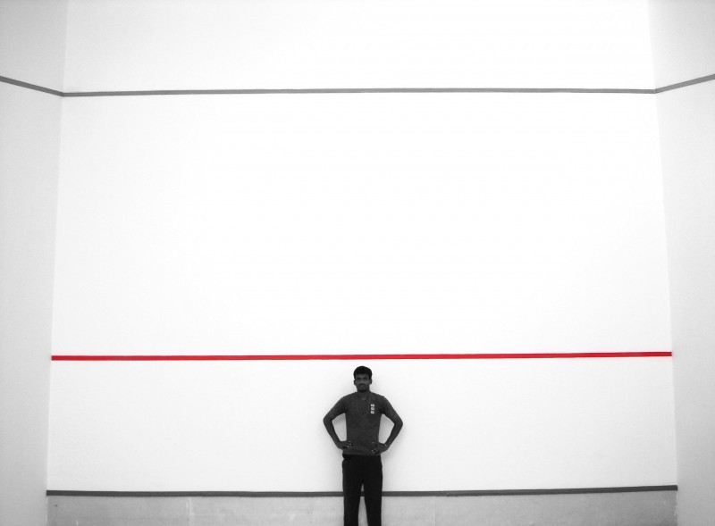 this man standing in squash court for me