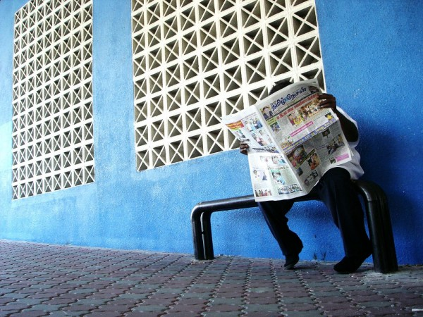 a man reading newspaper at a bus stop
