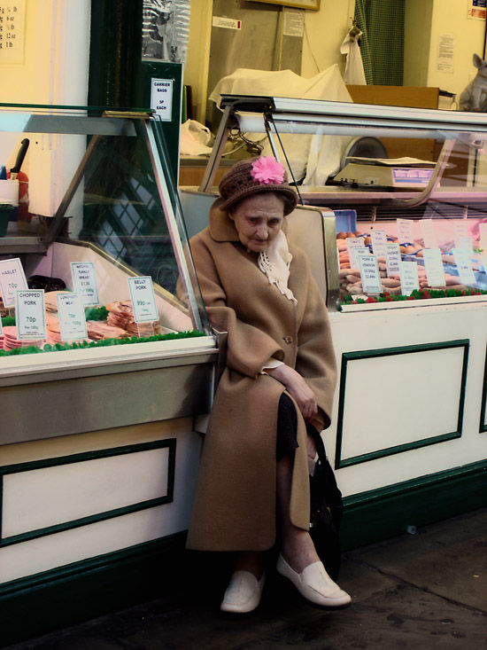 lonely grandmother sitting between market stalls