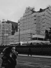 woman walking past a under construction building