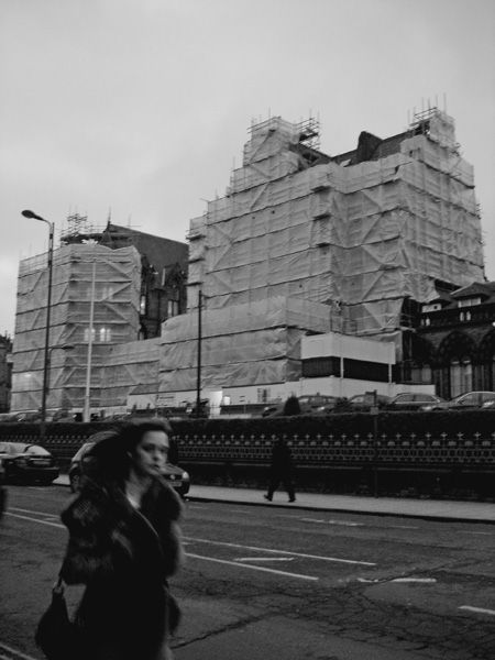 woman walking past a under construction building
