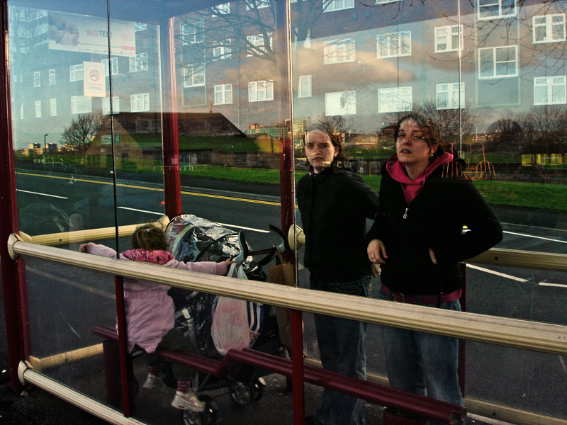 two woman with a child waiting at a leeds bus stop