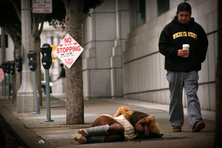 homeless woman sleeping on sidewalk