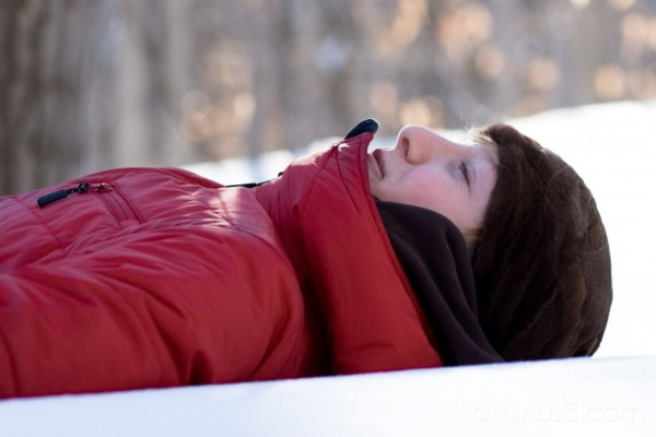 A girl resting on a blanket of snow