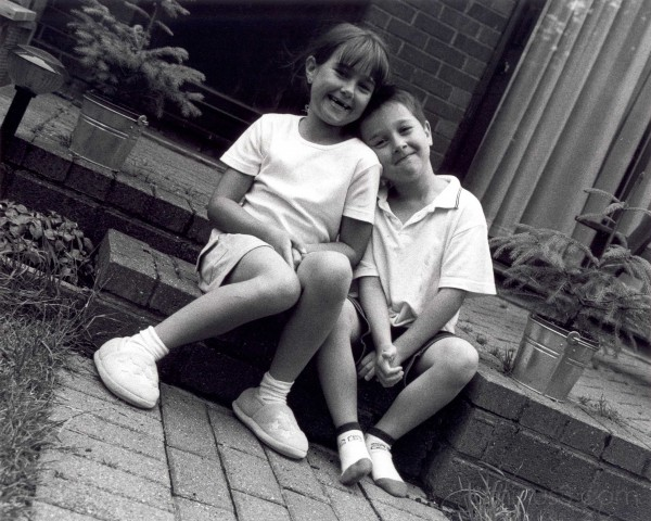 Laughing children sitting on step by Craig Brophy