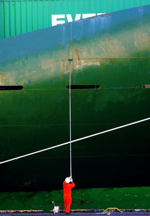 Dock worker painting ship in Yokohama