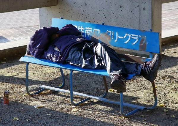 Homeless Japanese man asleep on bench