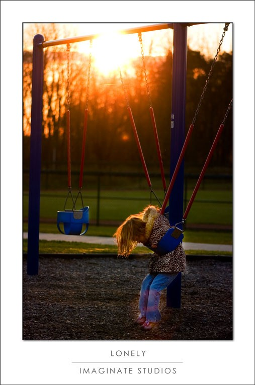 A photo of a girl on a swing.