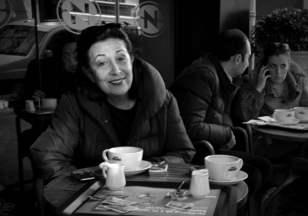 woman sitting drinking coffee at a cafe on street