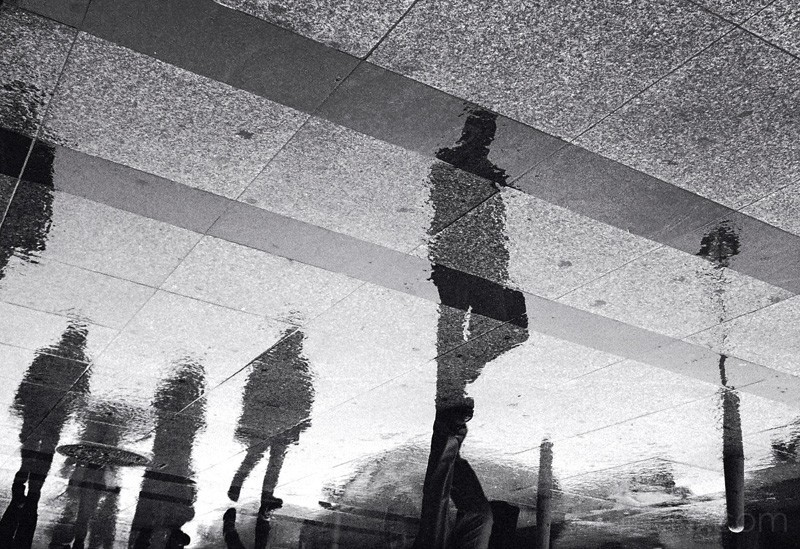 Reflections of people walking in the rain