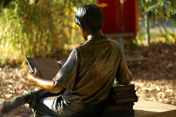 statue of a boy reading