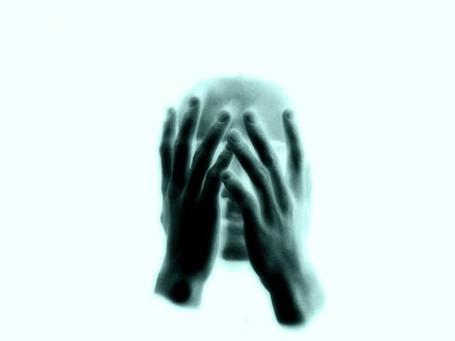 Human face hidden behind hands