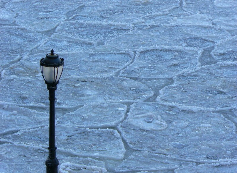 A lamp post overlooking ice patches in the water.