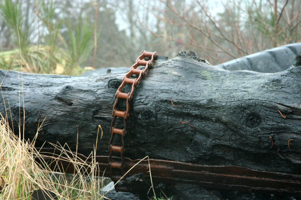 Rusty metal on old log in dump