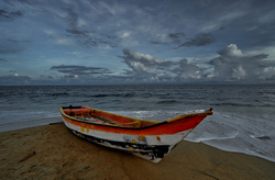 The lone boat and the rush of waves