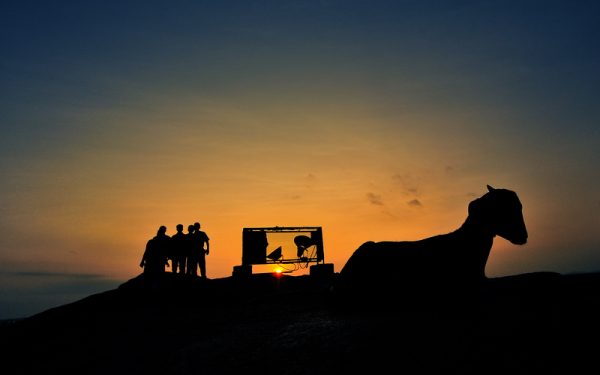 Goats, men and the hillock sunset