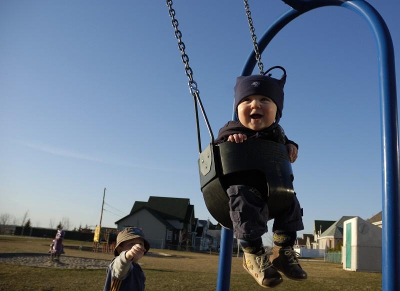 Thomas pushing Justin on the swing