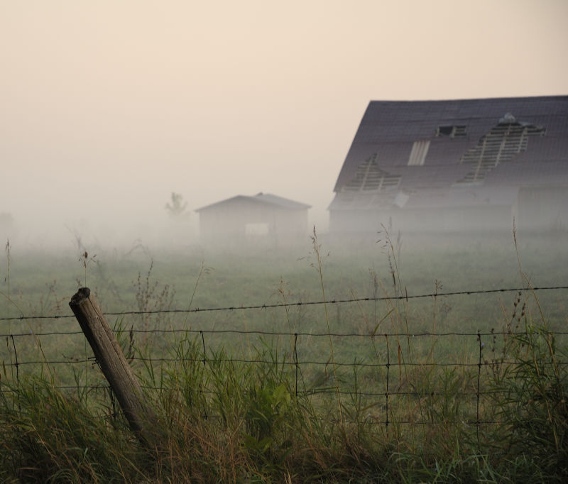 Old barn by a foggy morning