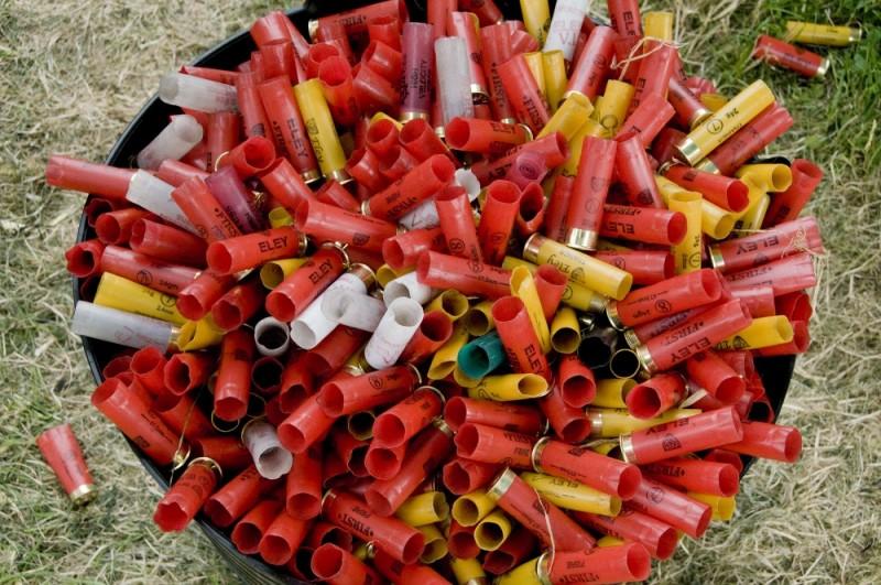 A BUCKET FULL OF USED GUN CARTRIDGES