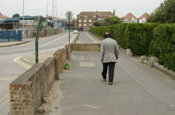 MAN WALKING DOWN A ROAD IN HOVE