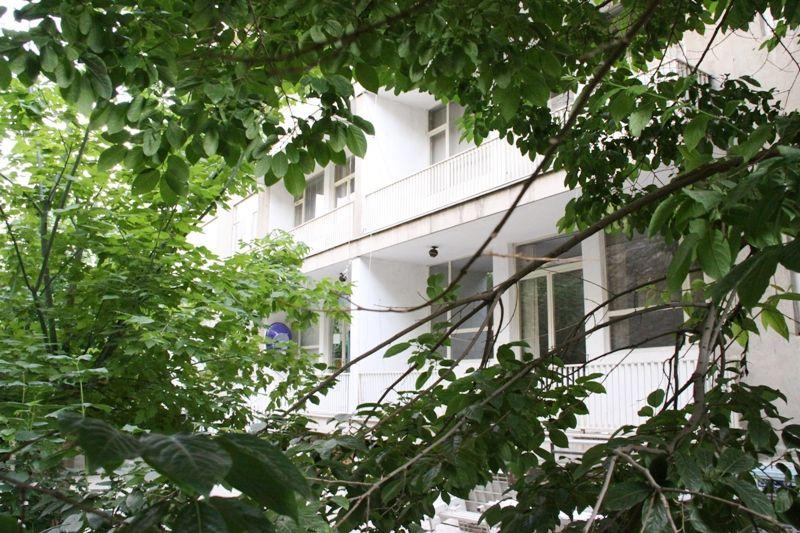 نمای ساختمان دانشکده خبر از پشت درخت های حیاط