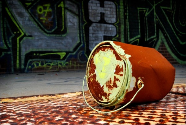 Old, rusty paint can in front of graffiti.