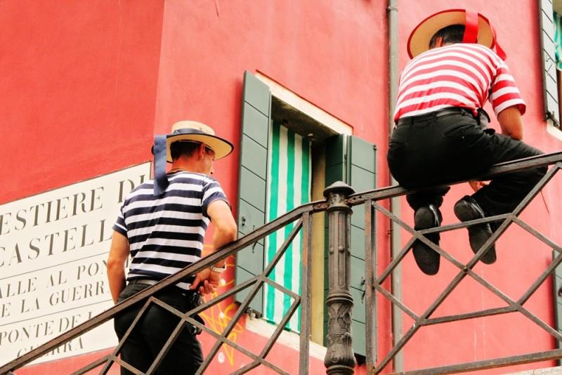 two gondola guys sitting on the bridge in Venice