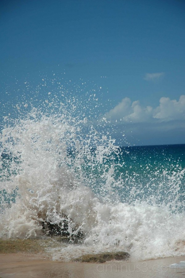 surf crashing on golden sand beach molokai
