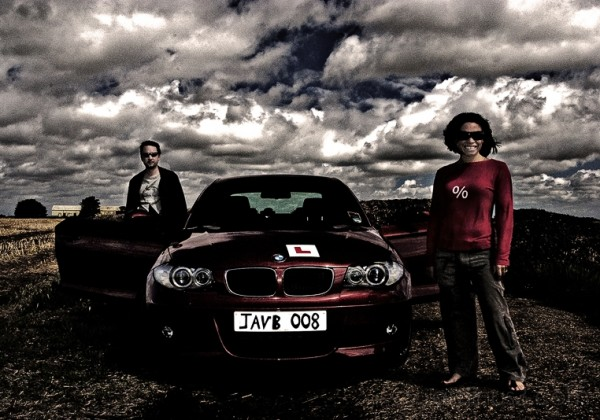 A man and woman in front of a BMW 123d Msport