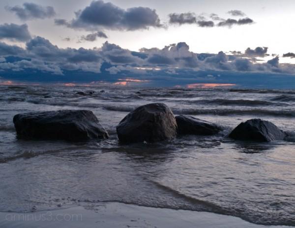 lake winnipeg rolls against beach rocks victoria b
