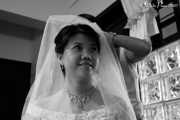 bride putting on the veil in black and white