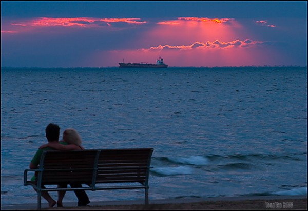 Lovers watch their dream cruise ship in the sunset