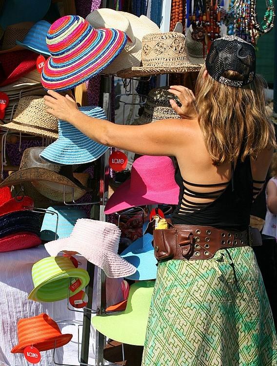 A sales assistant arranges her hats