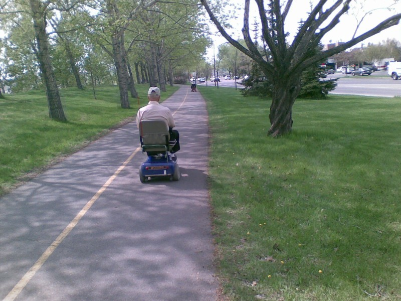 Seniors on electric scooters on Bow River Path