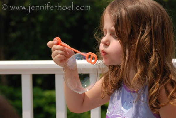 photo of a little girl blowing a bubble