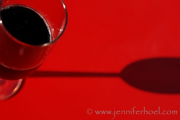 photo of red sparkling wine on a red table