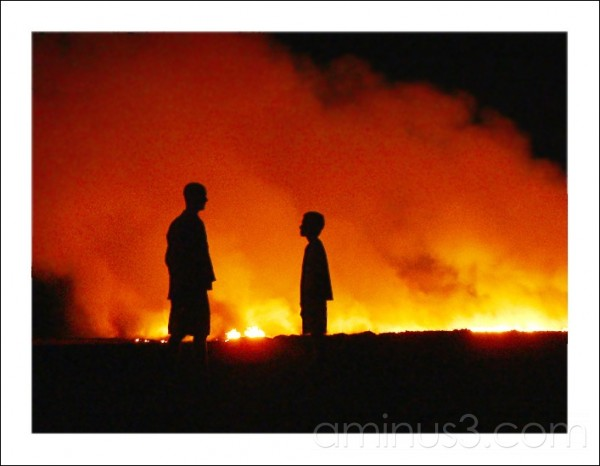 Father and son at a cane burning in Qld