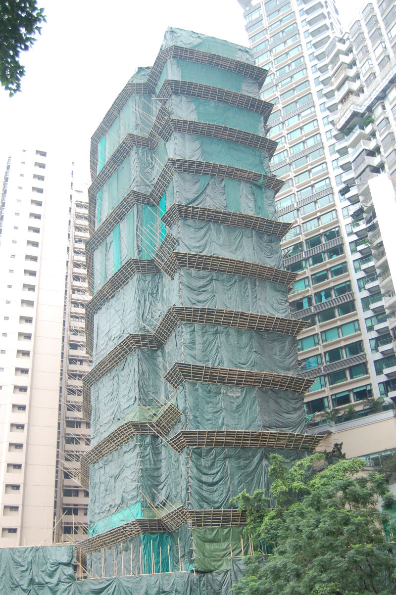a skyscraper being built with bamboo scaffolding