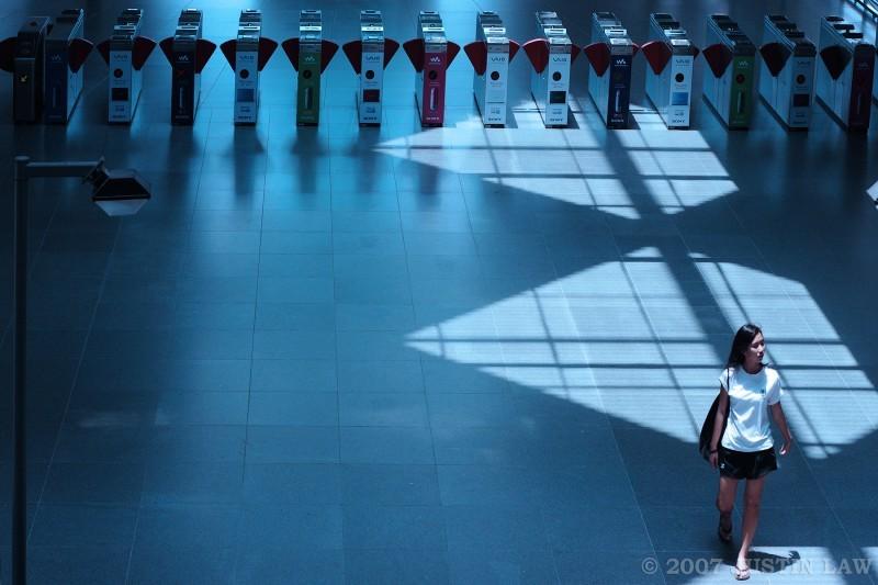 Girl walking through train station in blue